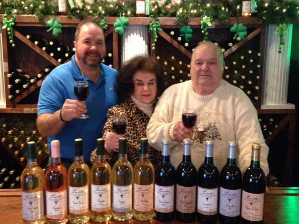vineyards the famiile lucchi at the tasting bar a glass of red wine by hand and assortment of bottles of wine from the vineyard in front of them lucchi family wine cellars scranton pennsylvania united states ulocal local products local purchase local produce locavore tourist