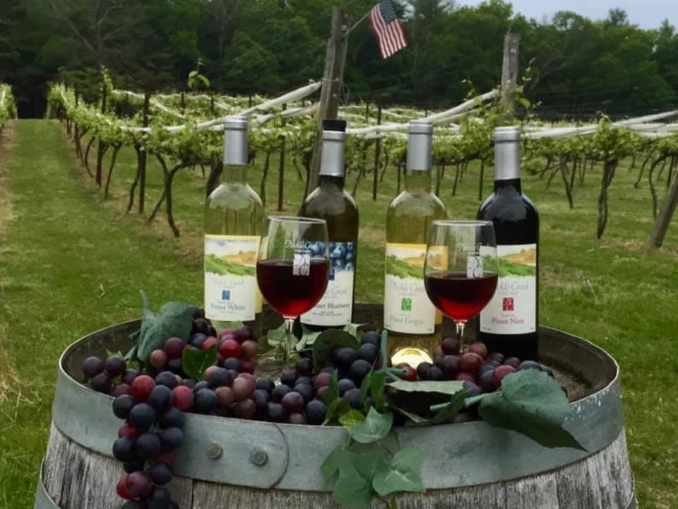 vineyards 2 bottles and glasses of red and white wine on a wooden barrel with bunch of red and green grapes in the vineyard nickle creek vineyard foster rhode island united states ulocal local products local purchase local produce locavore tourist