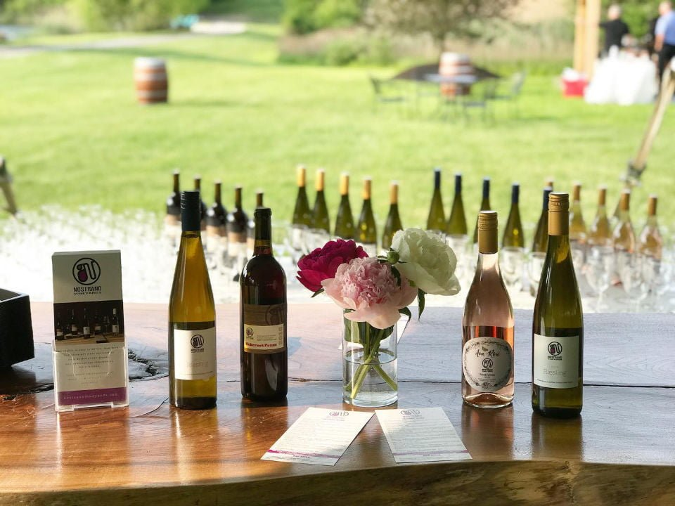 vineyards assortments of bottles and glasses of wine overlooking the vineyards nostrano vineyards milton new york united states ulocal local products local purchase local produce locavore tourist