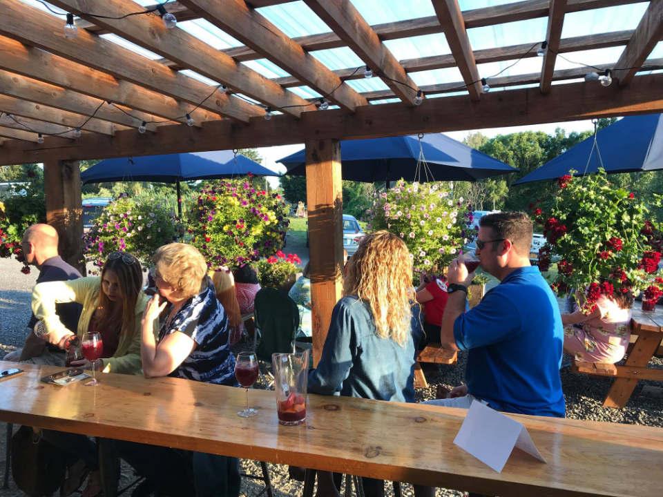vignoble gens au bar sur la terrasse journée ensoleillée avec parasols bleus pailshop vineyards fly creek new york états unis ulocal produits locaux achat local produits du terroir locavore touriste