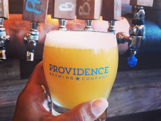 microbreweries glass of craft beer in one hand with beer dispenser in background providence brewing company north providence rhode island united states ulocal local products local purchase local produce locavore tourist
