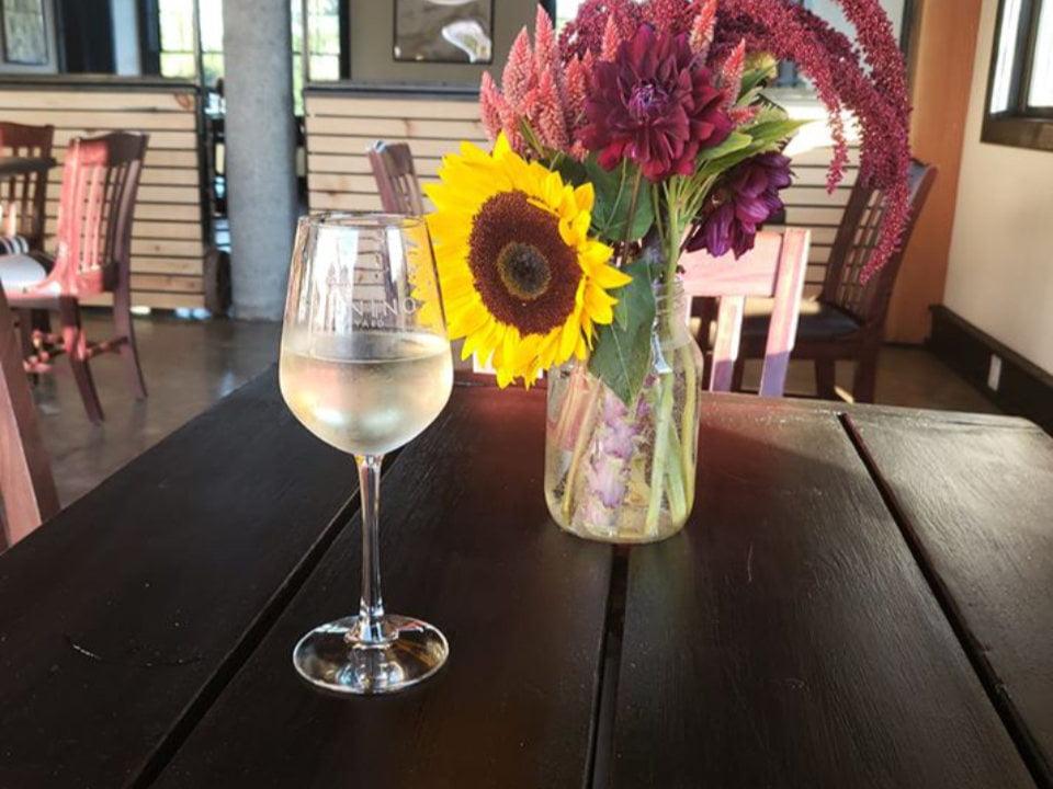 vignoble verre de vin blanc sur une table à côté d'un pôt de fleurs dans la salle de dégustation sannino vineyard cutchogue new york états unis ulocal produits locaux achat local produits du terroir locavore touriste