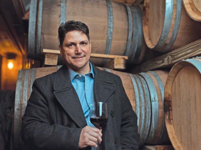 vignoble anthony sannino propriétaire du vignoble avec un verre de vin rouge dans ses mains dans la cave à vin tonneaux de bois sannino vineyard cutchogue new york états unis ulocal produits locaux achat local produits du terroir locavore touriste