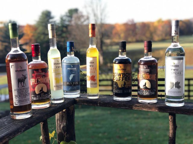 liquor assortment of spirits bottles on the edge of the fence with view of the field in the background springbrook hollow farm queensbury new york united states ulocal local products local purchase local produce locavore tourist