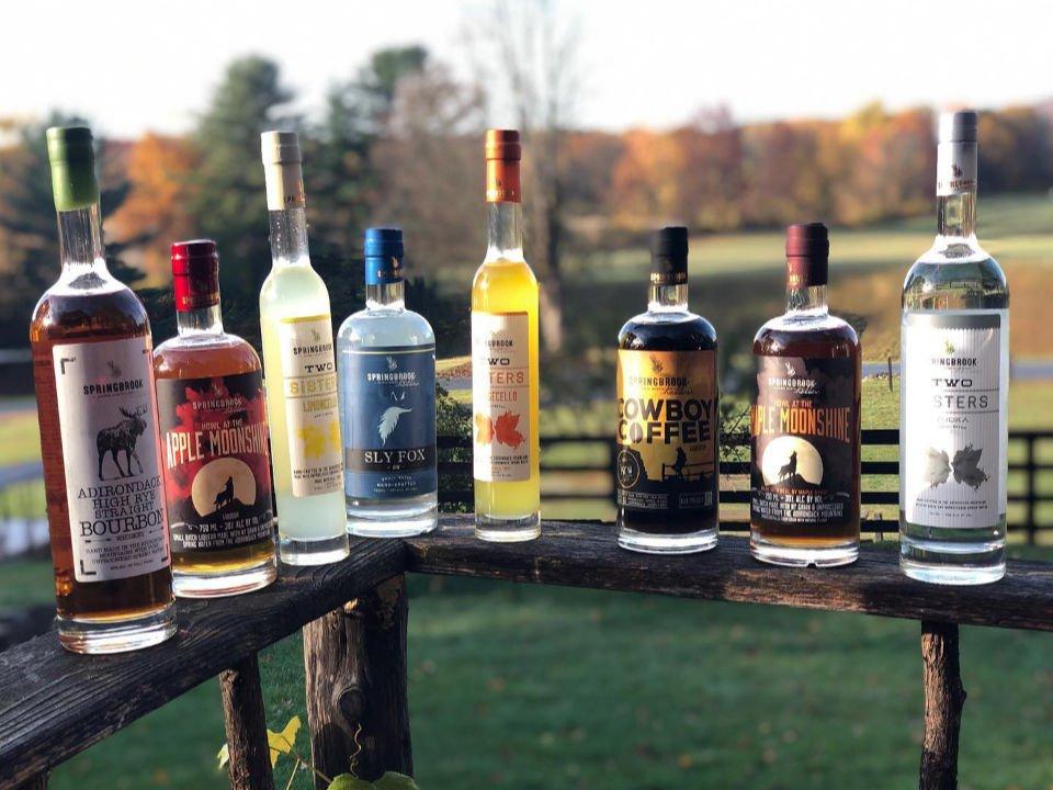 alcool assortiment de bouteilles de spiritueux sur le bord de la clôture avec vue du domaine en arrière plan springbrook hollow farm queensbury new york états unis ulocal produits locaux achat local produits du terroir locavore touriste
