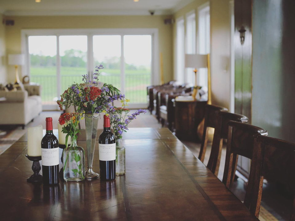 vineyards tasting room with large wooden table and sofas on the edge of the window stone tower winery leesburg virginia united states ulocal local products local purchase local produce locavore tourist