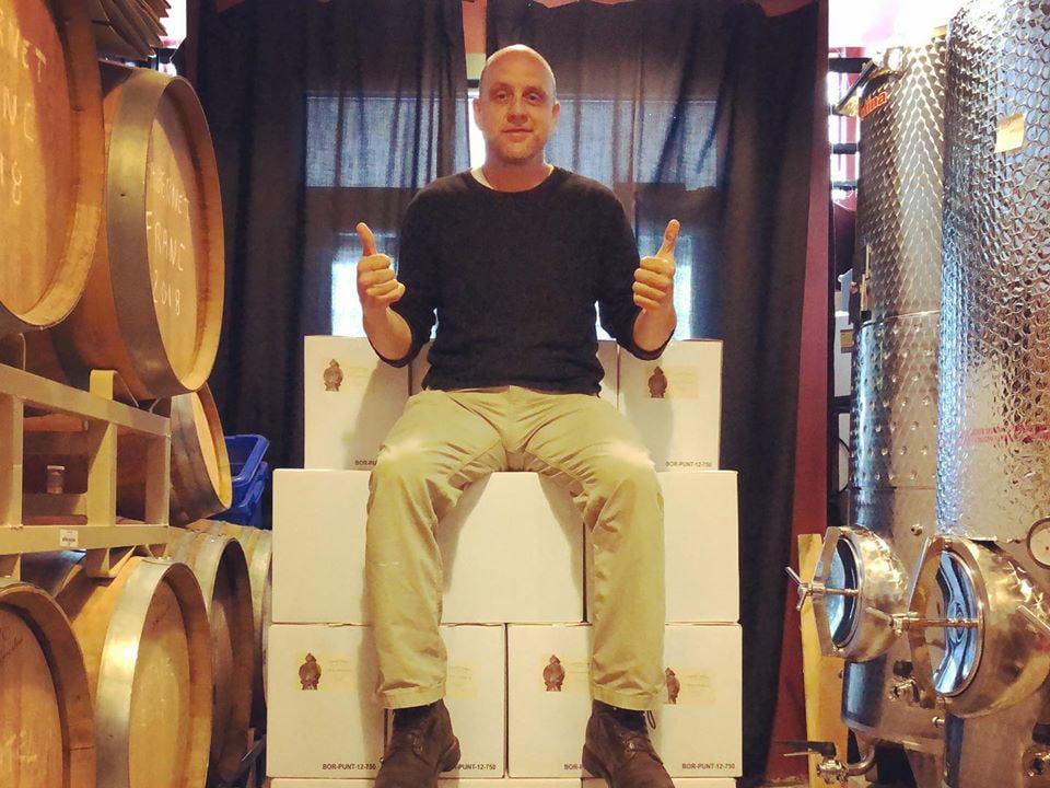 vignoble propriétaire assis sur des caisses de vin dans l'entrepôt avec tonneaux et réservoirs en acier inoxydable travessia winery new bedford massachusetts états unis ulocal produits locaux achat local produits du terroir locavore touriste