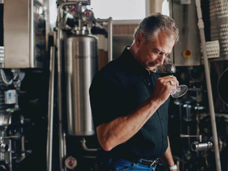 vineyards winemaker enjoying a glass of red wine in the wine production room with stainless steel tanks waltz vineyards estate winery manheim pennsylvania united states ulocal local products local purchase local produce locavore tourist