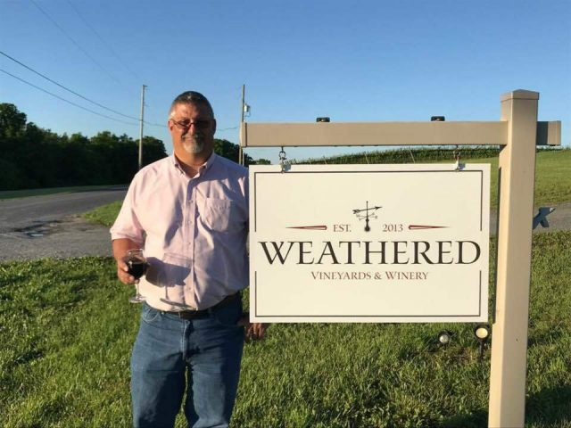 vineyards owner next to the vineyard sign a glass of wine in his hand weathered vineyards and winery new tripoli pennsylvania united states ulocal local products local purchase local produce locavore tourist