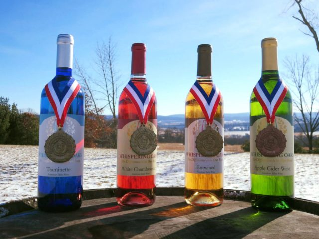 vineyards assortment of 4 award-winning wine bottles from the vineyard on a barrel outside in winter whispering oaks vineyard sunbury pennsylvania united states ulocal local products local purchase local produce locavore tourist