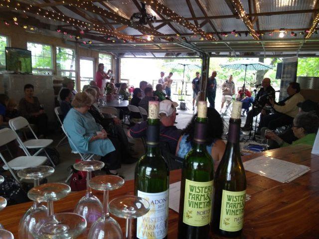 vignoble salle de dégustation remplie de clients avec portes de garage ouvertes wisteria farm and vineyard stanley virginie états unis ulocal produits locaux achat local produits du terroir locavore touriste