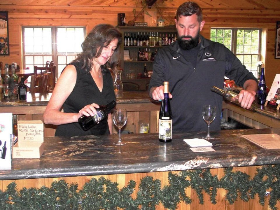 vineyards man and woman behind the tasting bar pouring a glass of wine woody lodge winery ashville pennsylvania united states ulocal local products local purchase local produce locavore tourist
