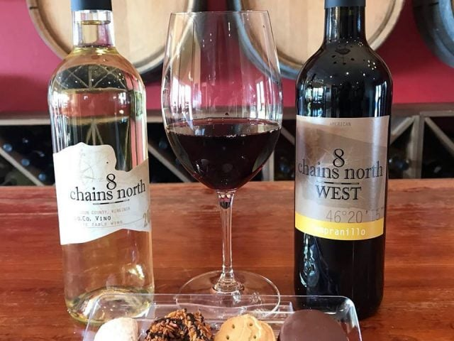 vineyards 2 bottles and 1 glass of red wine with cookie platter on a table in the cellar filled with barrels 8 chains north winery waterford virginia united states ulocal local products local purchase local produce locavore tourist