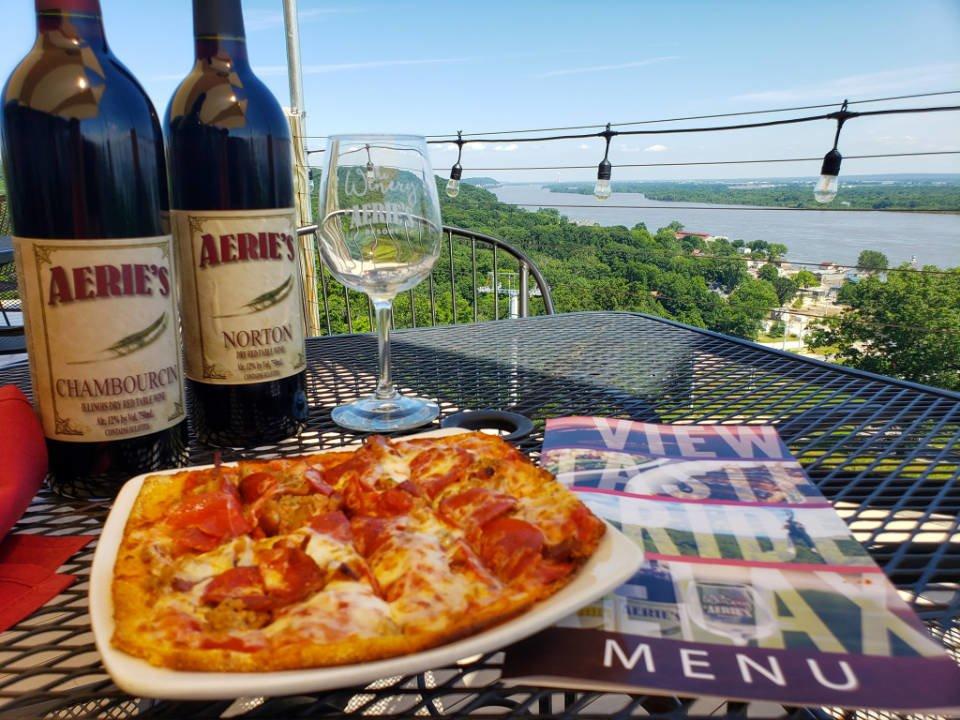 vignoble 2 bouteilles et verre de vin sur une table de la terrasse avec pizza et carte du menu avec vue en hauteur de la rivière du mississippi aeries winery grafton illinois états unis ulocal produits locaux achat local produits du terroir locavore touriste