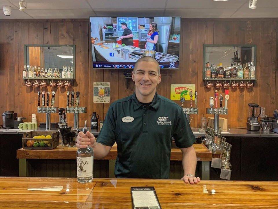 microbrasserie barman qui tient une bouteille en arrière de son bar barley creek tasting room and pub tannersville pennsylvanie états unis ulocal produits locaux achat local produits du terroir locavore touriste