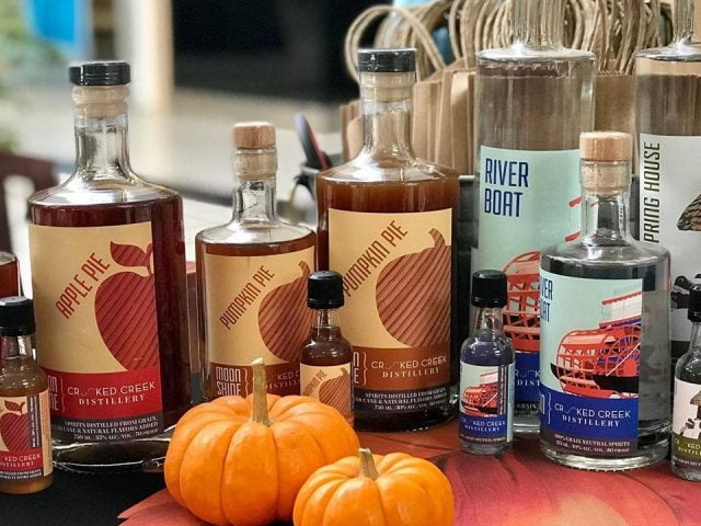 liquor bottles of different sizes of moonshine with various flavors and other spirits with 2 pumpkins crooked creek distillery west newton pennsylvania united states ulocal local products local purchase local produce locavore tourist