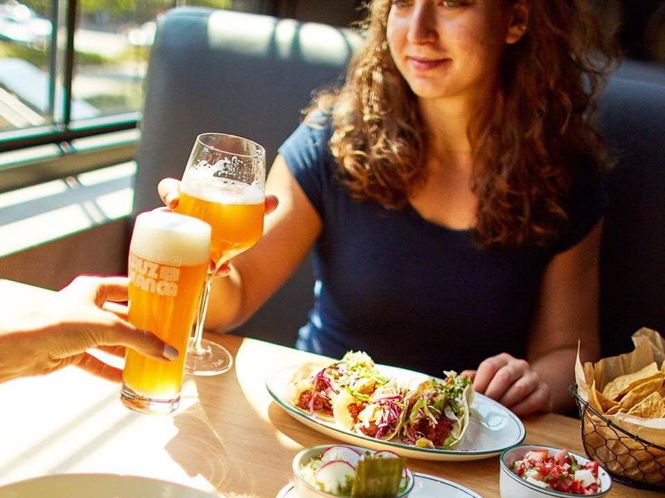 microbrasserie 2 personnes qui lèvent leur bière avec des tacos mexicains sur la table cruz blanca brewery and taqueria chicago illinois états unis ulocal produits locaux achat local produits du terroir locavore touriste
