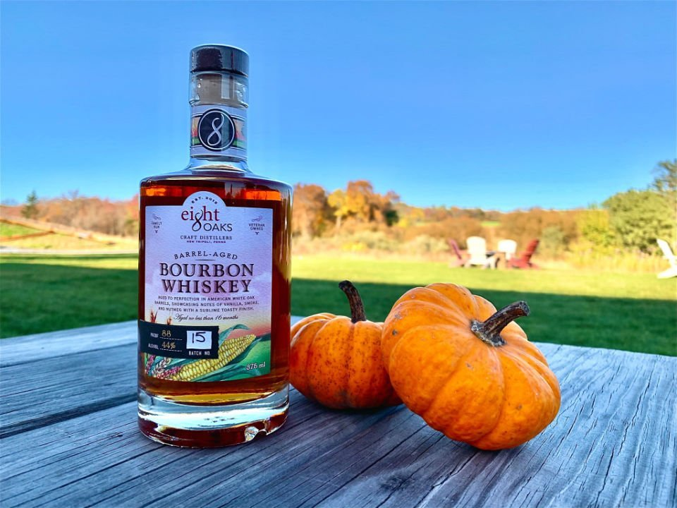 liquor bottle of bourbon whiskey on a picnic table with pumpkin and view of the field eight oaks farm distillery new tripoli pennsylvania united states ulocal local products local purchase local produce locavore tourist