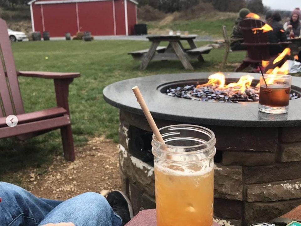 alcool gens assis autour d'un feu de pierre en prenant un cocktail eight oaks farm distillery new tripoli pennsylvanie états unis ulocal produits locaux achat local produits du terroir locavore touriste