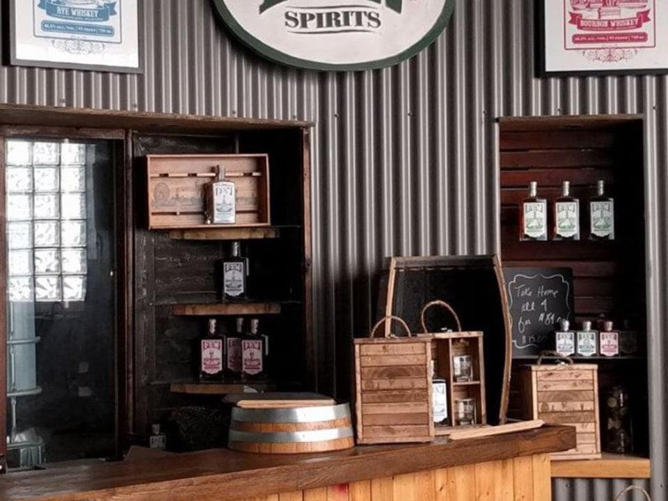 alcool comptoir et présentoirs en bois de spiritueux avec fenêtre vers la distillerie few spirits evanston illinois états unis ulocal produits locaux achat local produits du terroir locavore touriste