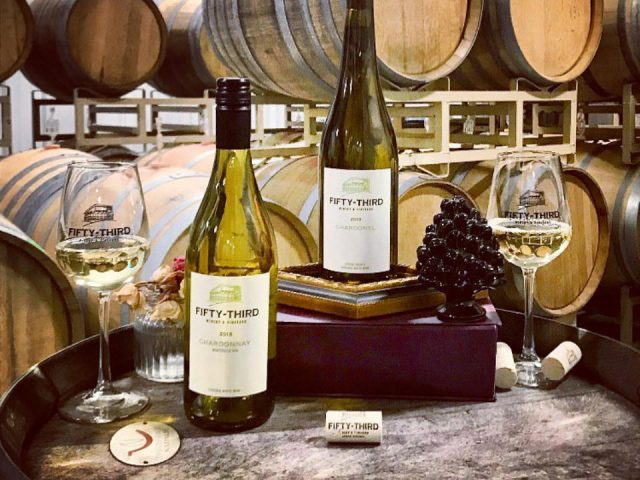 vineyards 2 bottles and 2 glasses of white wine on a wooden barrel in the cellar filled with barrels fifty-third winery and vineyard louisa virginia united states ulocal local products local purchase local produce locavore tourist