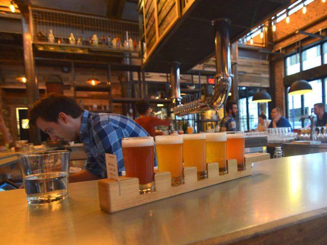 microbrasserie barman derrière son bar et un plateau de dégustation de bière avec clients autour du bar forbidden root columbus ohio états unis ulocal produits locaux achat local produits du terroir locavore touriste