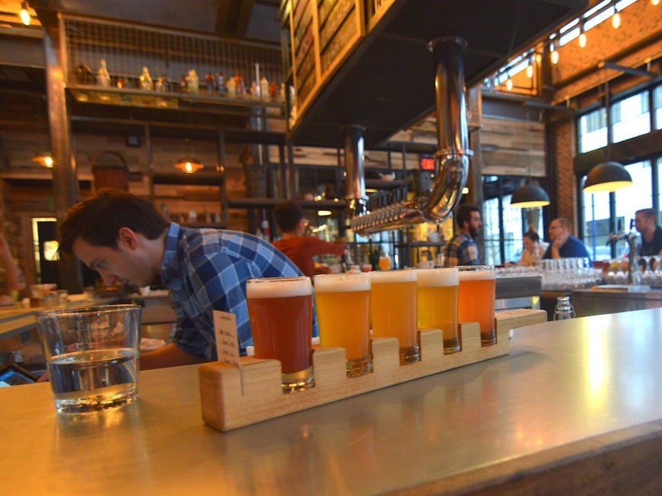 microbreweries barman behind his bar and a beer tasting tray with customers around the bar forbidden root columbus ohio united states ulocal local products local purchase local produce locavore tourist