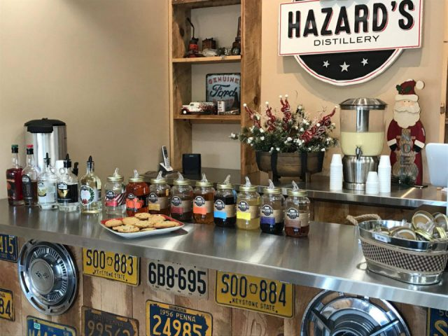 alcool bar de dégustation avec présentoir en bois et logo sur le mur et pots mason et bouteilles de spiritueux sur le bar en stainless hazards distillery mifflintown pennsylvanie états unis ulocal produits locaux achat local produits du terroir locavore touriste