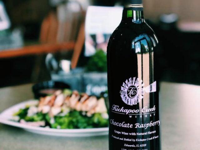 vignoble bouteille de vin chocolate raspberry avec salade césar au poulet en arrière-plan kickapoo creek winery edwards illinois états unis ulocal produits locaux achat local produits du terroir locavore touriste