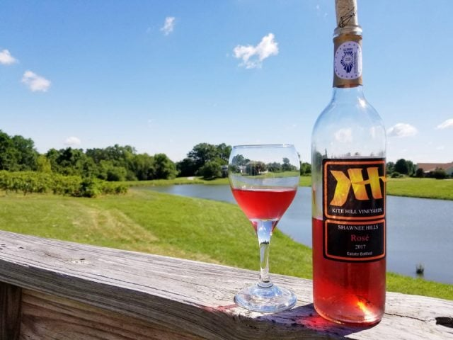 vineyards bottle and glass of rosé wine on the edge of the terrace and view of the pond in summer kite hill vineyards carbondale illinois united states ulocal local products local purchase local produce locavore tourist