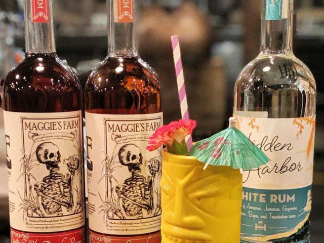 alcool bouteilles de différentes saveurs de rhum et cocktail avec un verre avec un totem jaune et une paille maggies farm rum distillery pittsburgh pennsylvanie états unis ulocal produits locaux achat local produits du terroir locavore touriste