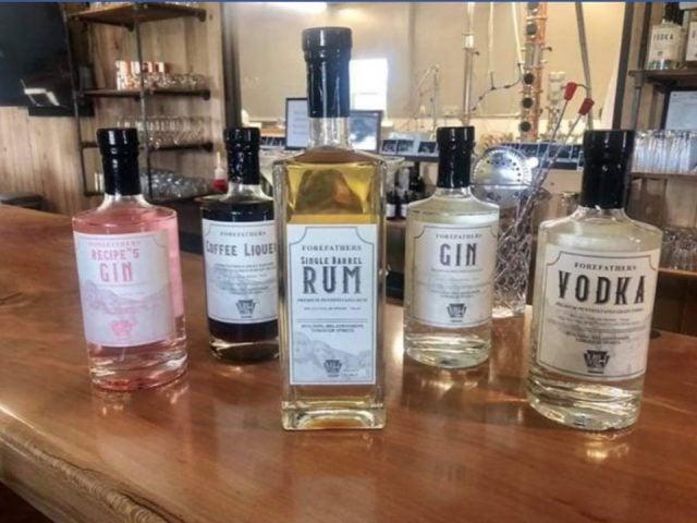 alcool bouteilles de gin vodka rhum sur le bar en bois et fenêtre sur la distillerie et alambic mlh distillery grove city pennsylvanie états unis ulocal produits locaux achat local produits du terroir locavore touriste