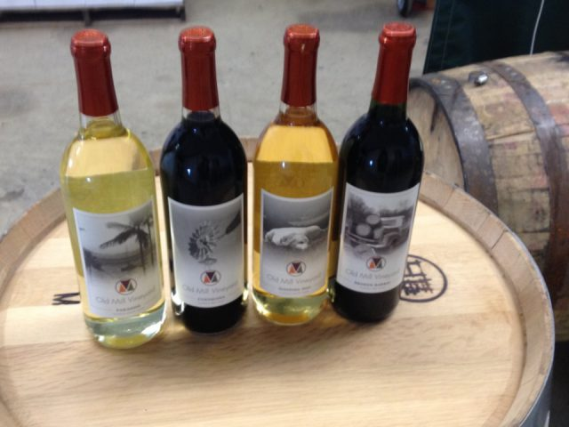 vineyards 4 bottles of wine from the vineyard on a wooden barrel in the cellar with wooden barrel next to it old mill vineyard metamora illinois united states ulocal local products local purchase local produce locavore tourist