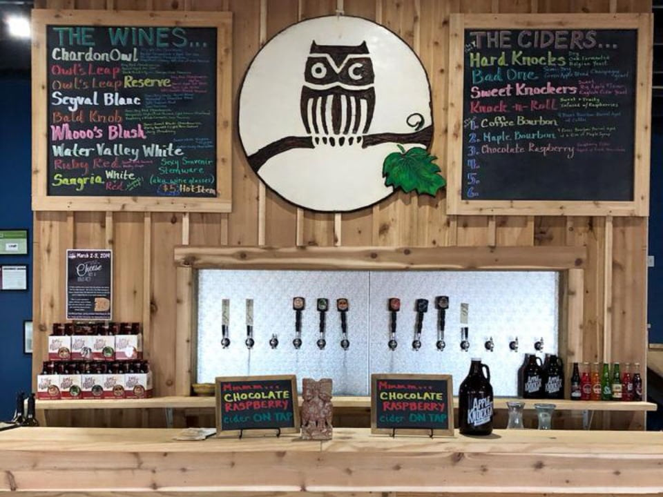 vineyards wooden tasting bar with cider dispenser and owl logo image on the wall between 2 chalk boards with specials owl creek vineyard cobden illinois united states ulocal local products local purchase local produce locavore tourist