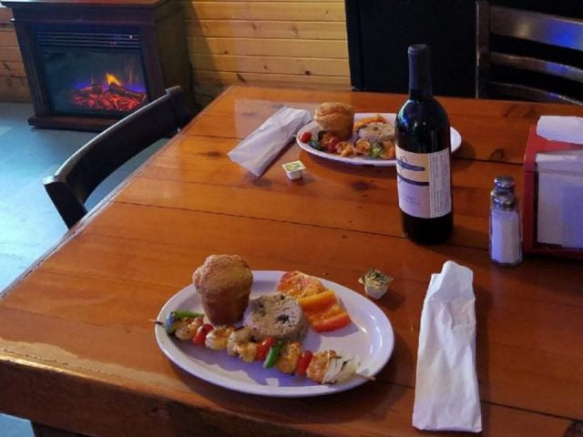 vineyards bottle of red wine with 2 plates of homemade meal on a wooden table plainview vineyard plainview illinois united states ulocal local products local purchase local produce locavore tourist