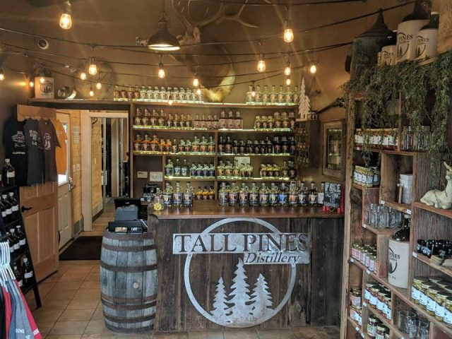 liquor distillery shop with items with logo and variety of spirits in display and wooden counter with logo tall pines distillery salisbury pennsylvania united states ulocal local products local purchase local produce locavore tourist
