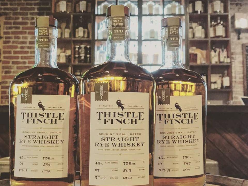 alcool 3 bouteilles de straight rye whiskey sur un tonneau de bois dans la salle de dégustation thistle finch distillery lancaster pennsylvanie états unis ulocal produits locaux achat local produits du terroir locavore touriste