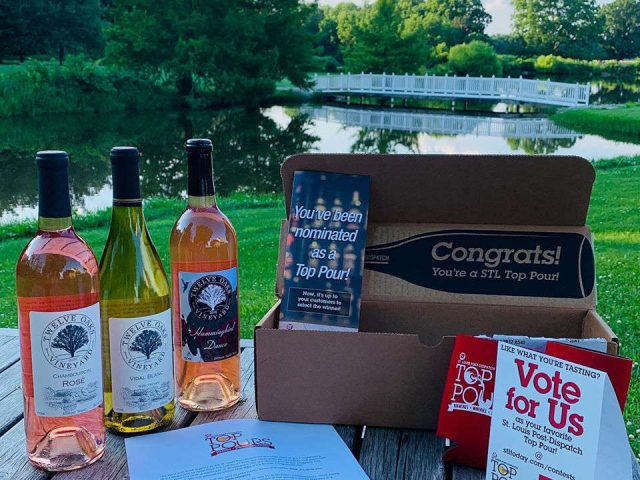 vineyards bottles of wine on a table in front of a pond with a white bridge and box with prices twelve oaks vineyard carlyle illinois united states ulocal local products local purchase local produce locavore tourist