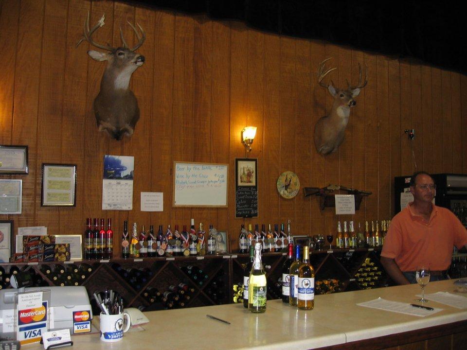 vignoble bar de dégustation avec personnel en arrière du bar avec bouteilles de vin sur le bar et dans le présentoir et 2 têtes de chevreuils empaillés sur le mur vahling vineyards stewardson illinois états unis ulocal produits locaux achat local produits du terroir locavore touriste