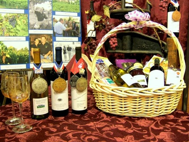 vineyards award-winning wine bottles and 2 glasses with basket of local produce and family photos valentino vineyards and winery long grove illinois united states ulocal local products local purchase local produce locavore tourist