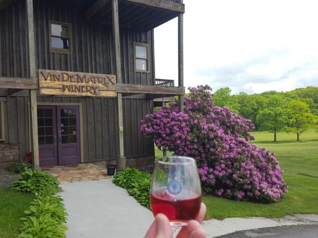 vineyards entrance to the winery in an old wooden barn and glass of wine with beautiful flower decor and golf course in summer vin de matrix winery rockwood pennsylvania united states ulocal local products local purchase local produce locavore tourist