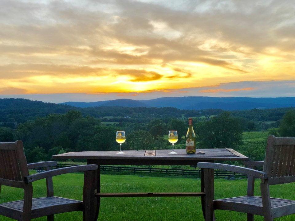 vignoble 2 verres et une bouteille de vin blanc sur une table avec 2 chaises avec magnifique vue du domaine barrel oak winery delaplane virginie états unis ulocal produits locaux achat local produits du terroir locavore touriste