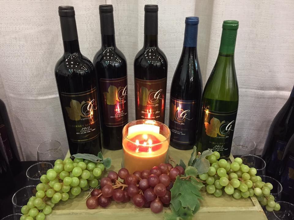 vignoble assortiment de 5 bouteilles de vin sur une planche avec grappes de raisins rouges et verts avec chandelle castle glen estates winery doswell virginie états unis ulocal produits locaux achat local produits du terroir locavore touriste