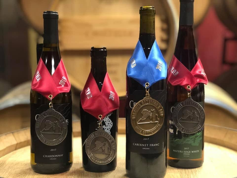 vineyards assortment of award-winning wine bottles with barrels in the background creeks edge winery lovettsville virginia united states ulocal local products local purchase local produce locavore tourist