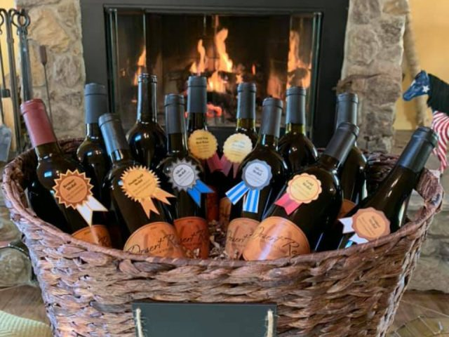 vineyards assortment of wine bottles in a basket in front of the fireplace desert rose ranch and winery hume virginia united states ulocal local products local purchase local produce locavore tourist
