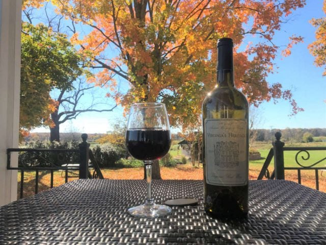 vineyards bottle and glass of red wine on a terrace table with a view of the estate and trees in autumn colors effingham manor winery nokesville virginia united states ulocal local products local purchase local produce locavore tourist