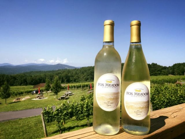 vineyards 2 bottles of white wine on the edge of the terrace with a view of the estate with picnic tables and vines fox meadow winery linden virginia united states ulocal local products local purchase local produce locavore tourist