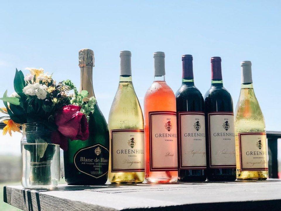 vignoble assortiment de bouteilles de vin avec pot de fleur sur une table en plein-air greenhill winery and vineyards middleburg virginie états unis ulocal produits locaux achat local produits du terroir locavore touriste