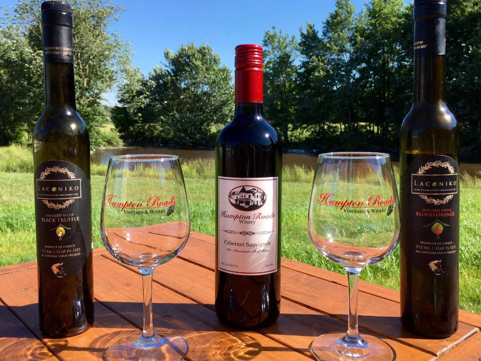 vineyards assortment of 3 bottles and 2 glasses of wine on a picnic table in front of a pond hampton roads winery elberon virginia united states ulocal local products local purchase local produce locavore tourist