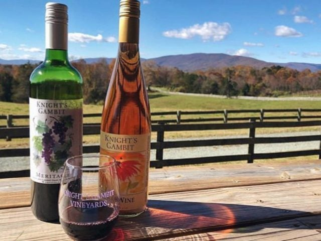 vineyards 2 bottles and a glass of wine on an outdoor table with a view of the fenced estate and mountains knights gambit vineyard charlottesville virginia united states ulocal local products local purchase local produce locavore tourist